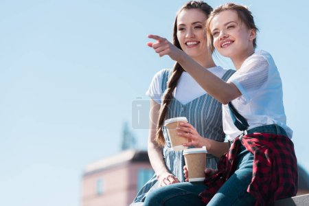 young woman pointing by finger to smiling female friend with paper cup of coffee