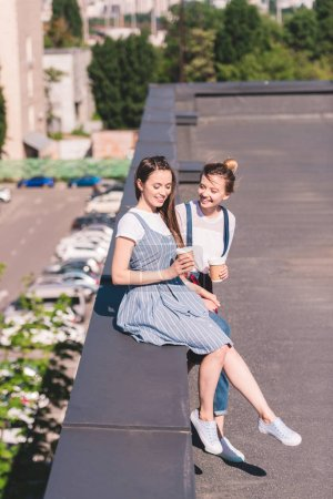 high angle view of young female friends with paper cups of coffee at rooftop