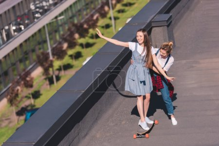 high angle view of woman teaching her female friend riding on skateboard at rooftop
