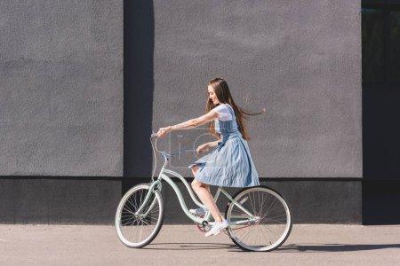 Photo pour Vue latérale d'une jeune femme heureuse, à cheval sur le vélo - image libre de droit