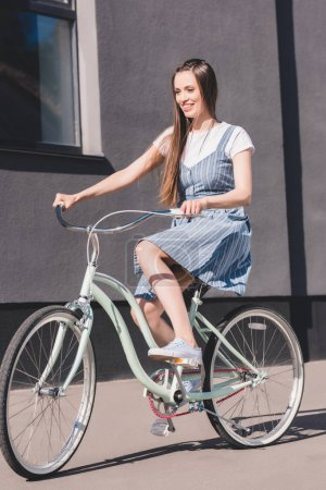 Photo for Front view of young smiling woman riding on bicycle - Royalty Free Image