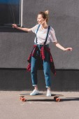 side view of happy young woman riding on skateboard