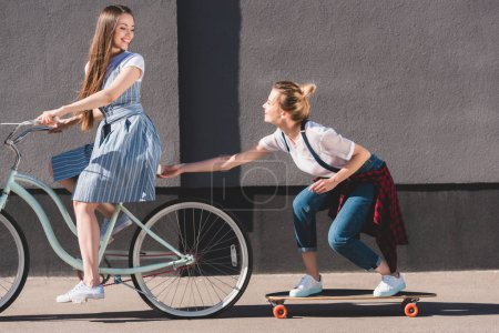 smiling woman riding bicycle and towing her female friend on skateboard