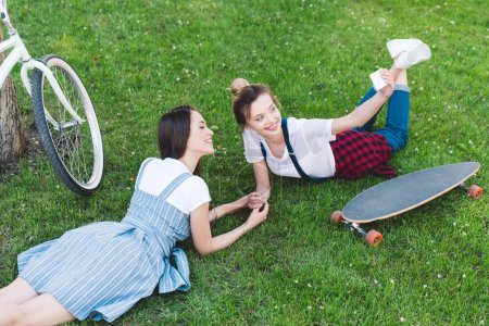 high angle view of smiling woman taking selfie on smartphone with female friend on grass with skateboard and bicycle in park