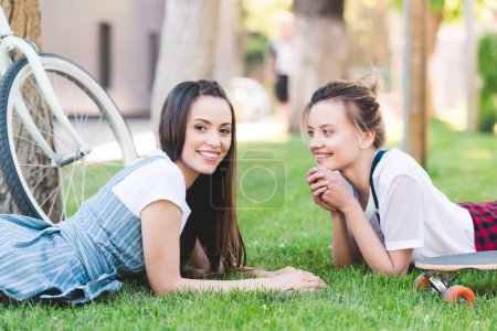 smiling female friends laying on grass with bicycle and skateboard in park