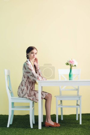 beautiful teen girl with braids sitting at table with flowers, on yellow