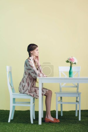 stylish teen girl with braids sitting at table with flowers, on yellow