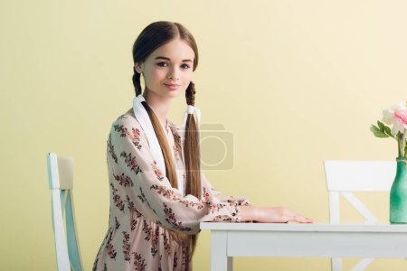 teen girl in summer dress with braids sitting at table with flowers, isolated on yellow