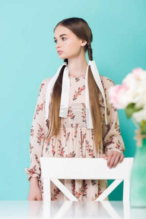 beautiful girl with braids posing near table with flowers, isolated on blue