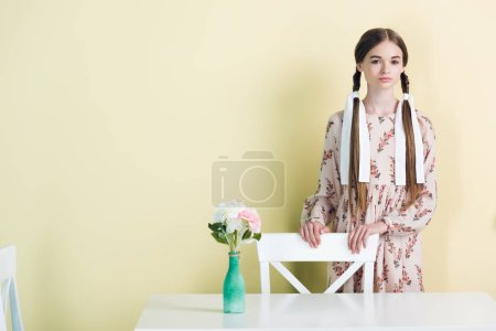 attractive teen girl with braids standing at table with flowers, on yellow