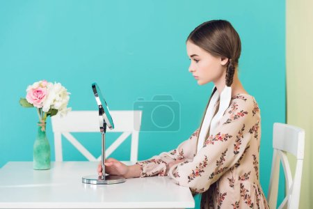 teen girl with braids looking at mirror while sitting at table with flowers, isolated on blue