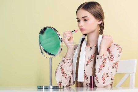 elegant teen girl applying lipstick with mirror, isolated on yellow