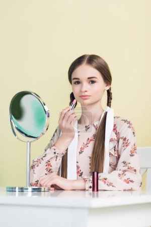 stylish youth girl applying lipstick with mirror, isolated on yellow