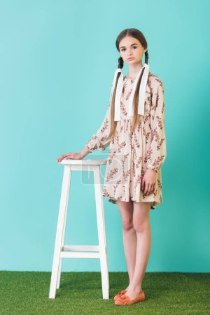 fashionable teen girl in summer dress with braids standing near stool, on blue
