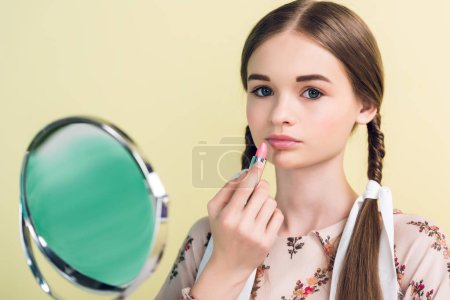 beautiful teen girl applying lipstick with mirror, isolated on yellow