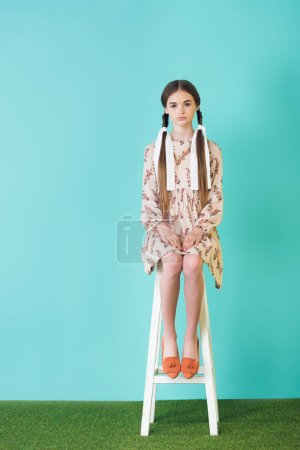 stylish teen girl in summer dress with braids sitting on stool, on turquoise