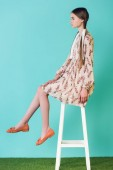 teen girl in summer dress with braids sitting on stool, on blue