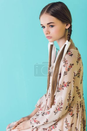 beautiful elegant teen girl with braids, isolated on turquoise