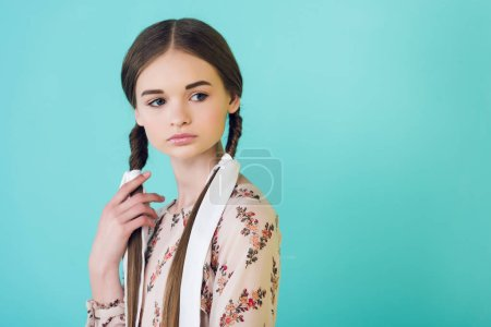 portrait of attractive elegant teen girl with braids, isolated on turquoise