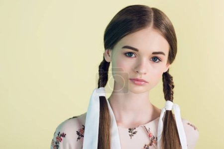 portrait of beautiful teen girl with braids, isolated on yellow