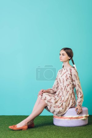 attractive youth girl sitting on big macaron, on turquoise
