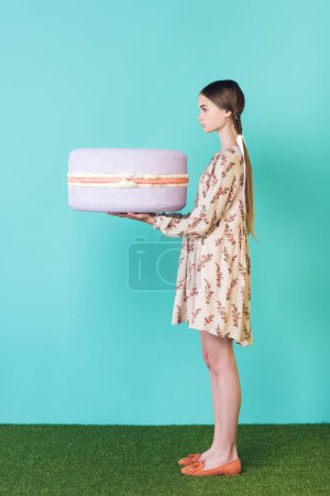 fashionable teen girl holding big purple macaron, on turquoise