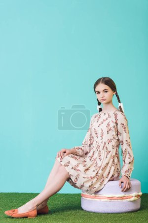 stylish elegant teen girl sitting on big macaron on blue