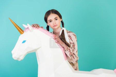fashionable youth girl posing with big white unicorn, isolated on blue