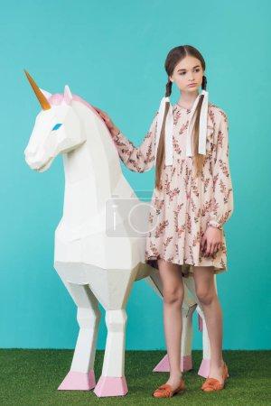 fashionable youth girl posing with big white unicorn on turquoise
