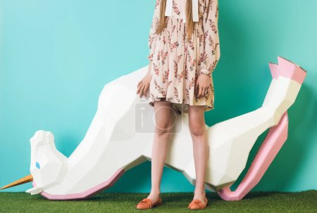 cropped view of model posing with big unicorn upside down, on blue