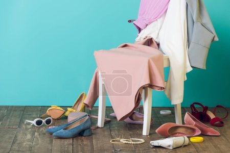 Photo for Messy room with elegant fashionable clothes and shoes on chair - Royalty Free Image
