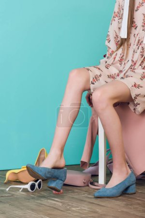 cropped view of girl in shoes sitting on chair with mess on floor