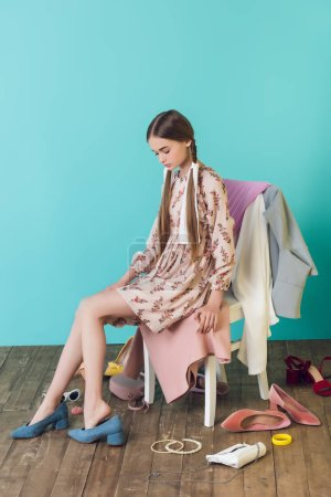 attractive youth girl sitting on chair with mess on floor