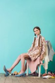 stylish teenager sitting on chair with mess of shoes and clothes