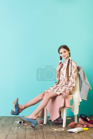 trendy teen girl sitting on chair with mess of shoes and clothes