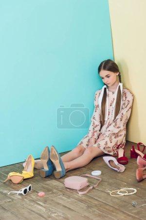 upset fashionable teen girl sitting on floor with mess