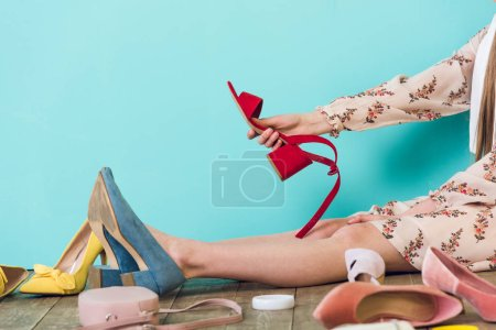 cropped view of girl sitting on floor with shoes