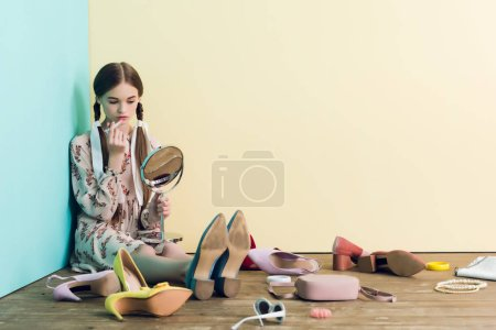 teen girl applying makeup with mirror and sitting on floor with mess