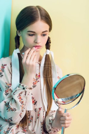 beautiful teen girl with braids applying lipstick with mirror