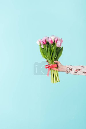 partial view of girl holding bouquet of tulips, isolated on turquoise