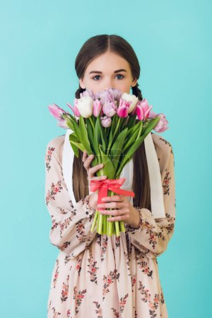 attractive girl in summer dress holding bouquet of tulips, isolated on blue