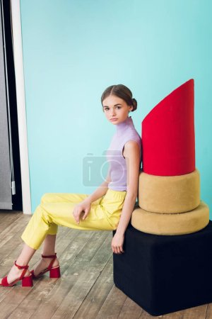attractive teen girl posing with big red lipstick for fashion shoot