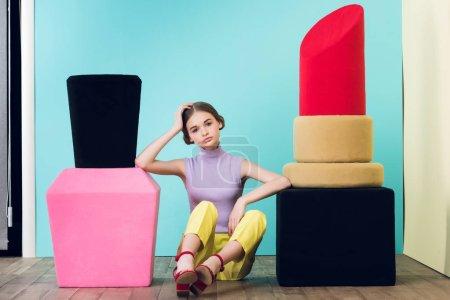 Photo pour Attrayant adolescent fille assis entre gros vernis à ongles et rouge à lèvres - image libre de droit