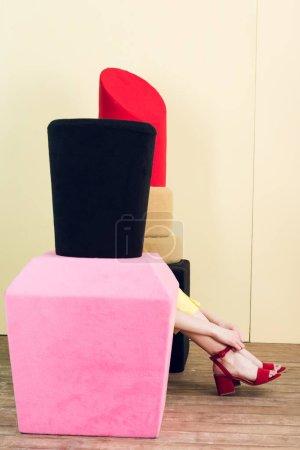 partial view of girl sitting near big nail polish and lipstick