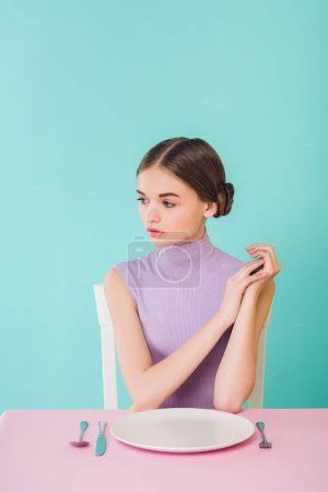 beautiful female teenager sitting at table with empty plate
