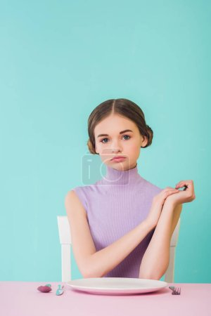 beautiful trendy girl sitting at table with empty plate