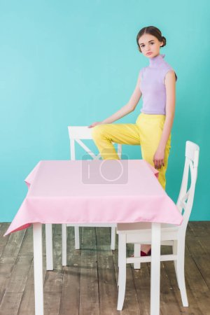 fashionable teen girl posing at table and chairs in dining room