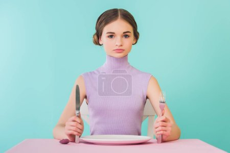 beautiful teen girl with knife, fork and empty plate sitting at table
