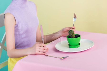 cropped view of teen girl eating cactus with fork and knife, diet concept
