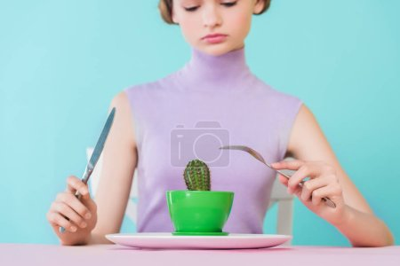 beautiful teen girl eating cactus with fork and knife, diet concept